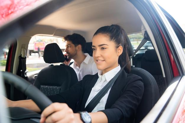 Portret van jonge vrouwelijke taxichauffeur met een zakenmanpassagier op achterbank. vervoer concept.