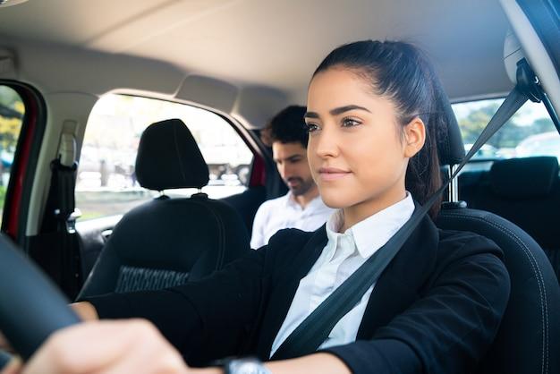 Portret van jonge vrouwelijke taxichauffeur met een zakenmanpassagier op achterbank