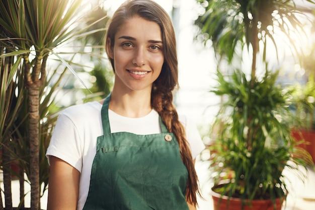 Portret van jonge vrouwelijke tuinman camera, eigenaar van een online winkel tuinbenodigdheden kijken