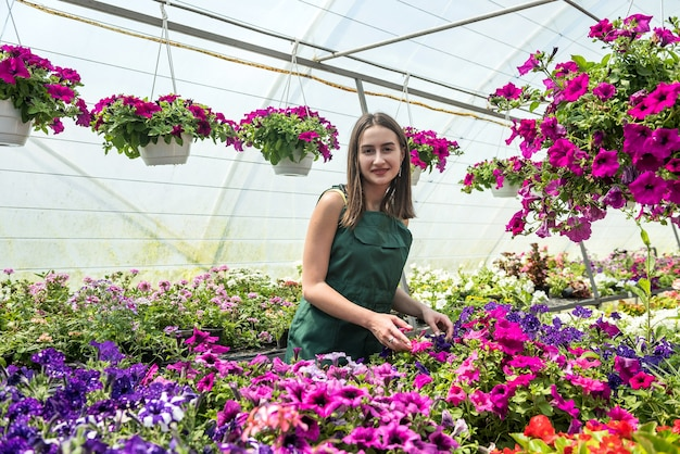 Portret van jonge vrouwelijke tuinman in schort werken met planten in potten in kas. botanische tuin