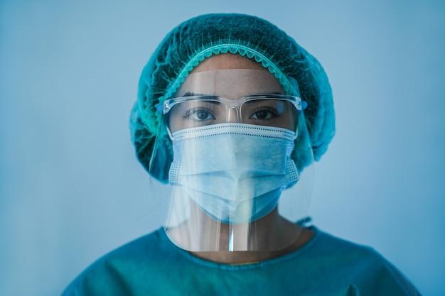 Portret van jonge vrouwelijke verpleegster die in het ziekenhuis werkt tijdens coronavirusperiode