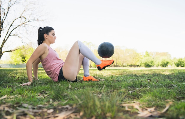 Portret van jonge vrouwelijke voetballer die en vaardigheden op voetbalgebied opleiden oefenen. sport concept.