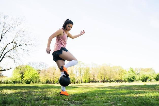 Portret van jonge vrouwelijke voetballer die kegels rondrennen tijdens het oefenen met de bal op het veld. sport concept.