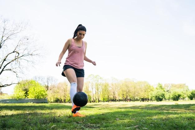 Portret van jonge vrouwelijke voetballer die kegels rondrennen tijdens het oefenen met de bal op het veld