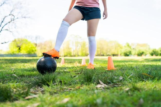 Portret van jonge vrouwelijke voetballer die kegels rondrennen tijdens het oefenen met de bal op het veld.