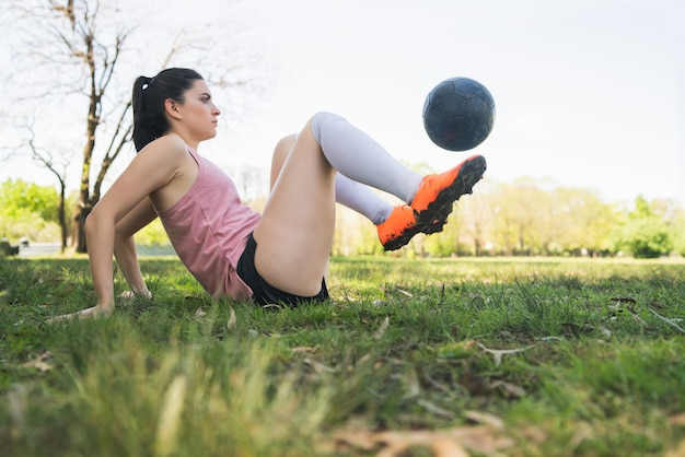 Portret van jonge vrouwelijke voetballer opleiding en het oefenen van vaardigheden op voetbalveld. sport concept.