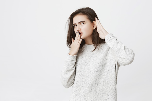 Portret van jonge vrouwelijke werknemer afluisteren of afluisteren iets, hand in hand in de buurt van mond en oor.