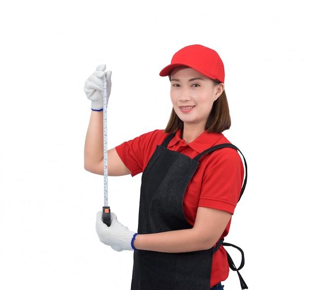 Portret van jonge vrouwenarbeider die in rode eenvormig met schort glimlachen, de holding die van de handschoenhand band meten die op witte backround wordt geïsoleerd