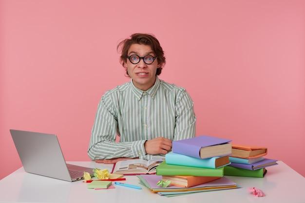 Portret van jonge wrokkige man met bril, draagt op een leeg shirt, zittend aan een tafel met boeken, werkt op een laptop, kijkt verward. geïsoleerd op roze achtergrond.