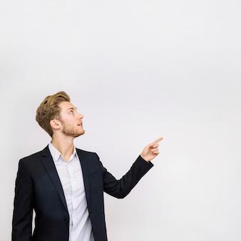 Portret van jonge zakenman die op iets richt dat omhoog eruit ziet