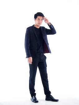 Portret van jonge zakenman in zwart pak op witte muur