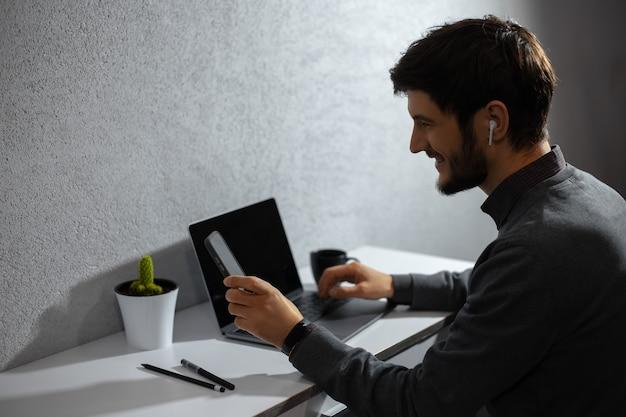Portret van jonge zakenman, met behulp van smartphone, laptop en andere benodigdheden voor kantoorwerk.
