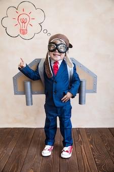 Portret van jonge zakenman met speelgoeddocument vleugels.