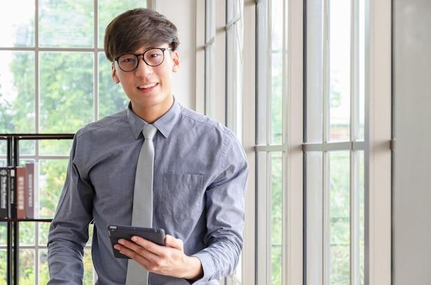 Portret van jonge zakenman met tabletpc in bureau met windlowlichten