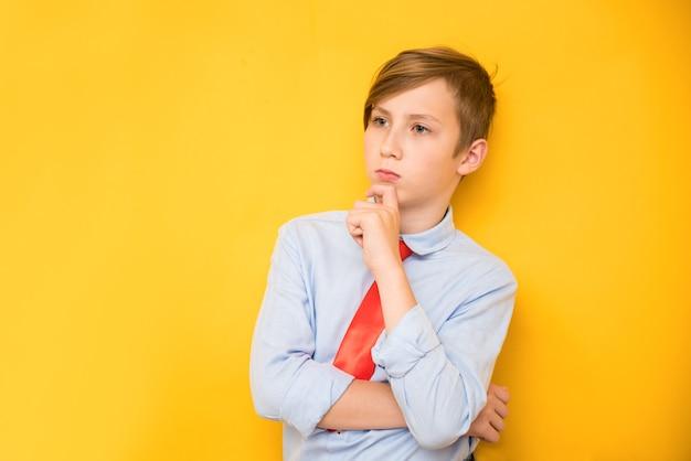 Portret van jonge zakenman van jongen in een overhemd. succesvolle tiener op een gele achtergrond