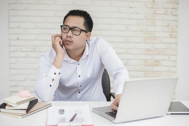 Portret van jonge zakenman zitten aan zijn bureau