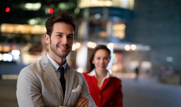 Portret van jonge zakenmensen 's nachts, zakenman en zakenvrouw samen