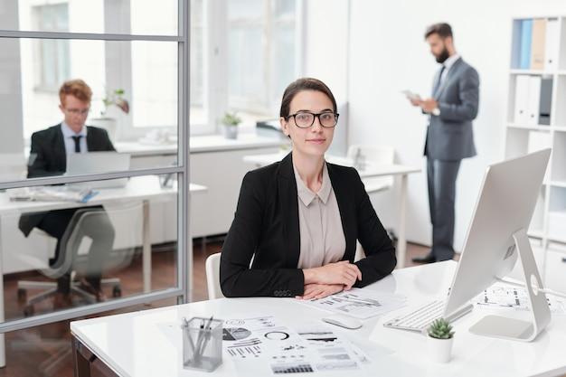 Portret van jonge zakenvrouw bril zittend aan de balie in kantoor, accountant of manager concept