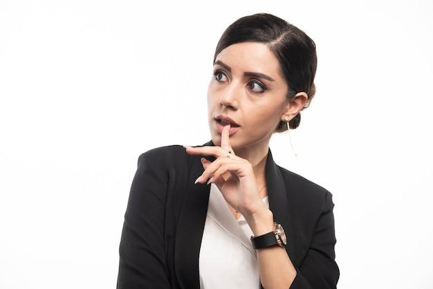 Portret van jonge zakenvrouw die zich voordeed op witte muur.