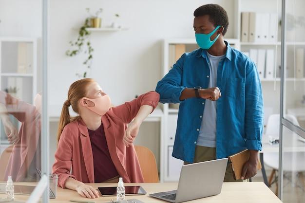 Portret van jonge zakenvrouw dragen masker stoten ellebogen met afro-amerikaanse collega als contactloze groet in post pandemie kantoor