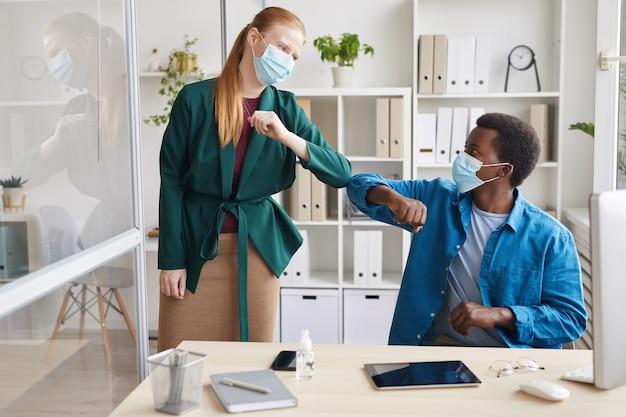 Portret van jonge zakenvrouw dragen masker stoten ellebogen met afro-amerikaanse man als contactloze groet in post pandemie kantoor