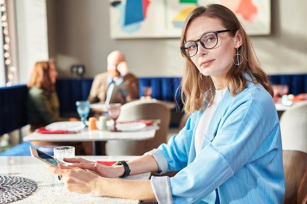 Portret van jonge zakenvrouw in stijlvolle jas zittend aan tafel in café en sociale media op tablet controleren