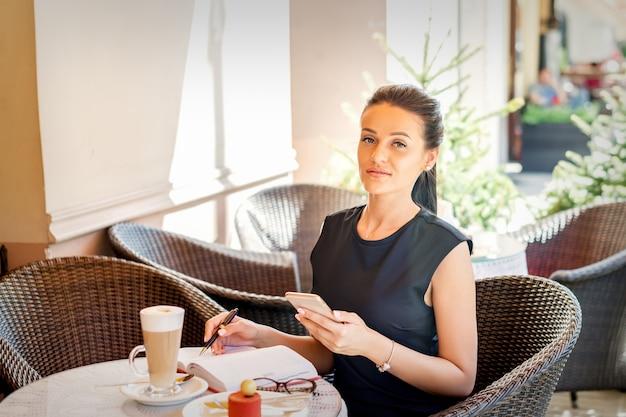 Portret van jonge zakenvrouw maakt aantekeningen in notitieblok van smartphone werken bij koffiepauze in café