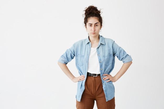 Portret van jonge zakenvrouw met donker haar in broodje dragen van casual kleding, op zoek met ergernis, staande met de handen op haar heupen, boos op haar werknemers met onbevredigende resultaten van het werk