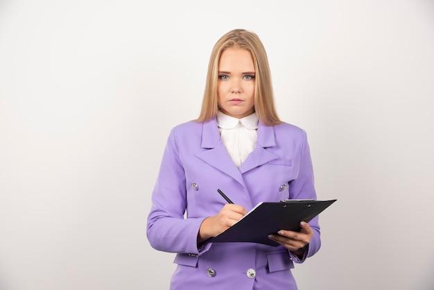 Portret van jonge zakenvrouw permanent en klembord te houden.