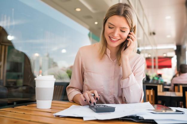 Portret van jonge zakenvrouw praten aan de telefoon tijdens het werken bij coffeeshop. bedrijfsconcept.