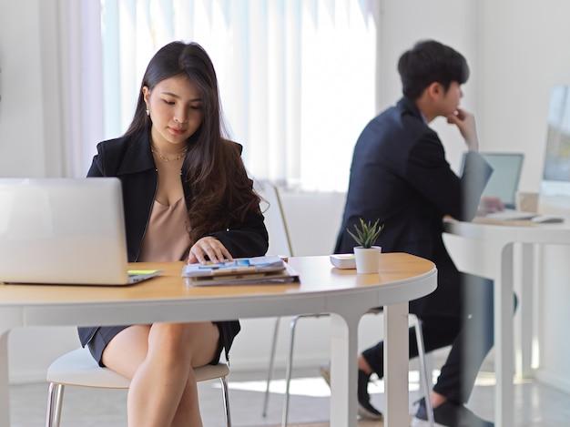 Portret van jonge zakenvrouw werken met laptop en papierwerk in kantoorruimte met collega