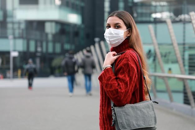 Portret van jonge zelfverzekerde vrouw buitenshuis beschermend masker dragen