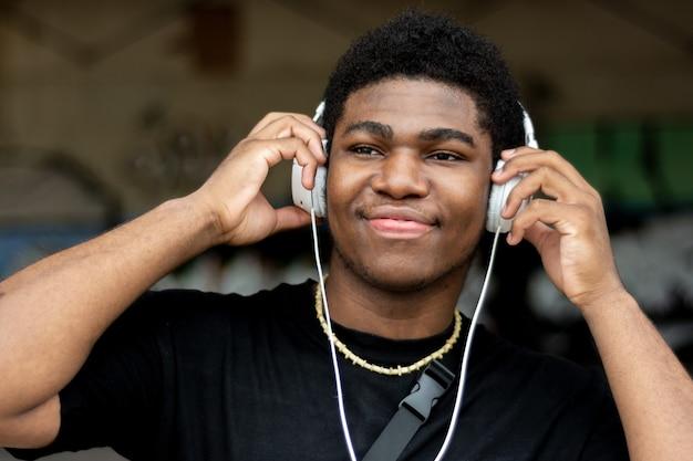Portret van jonge zwarte jongen met witte hoofdtelefoons. naar muziek aan het luisteren. graffiti muur achtergrond.