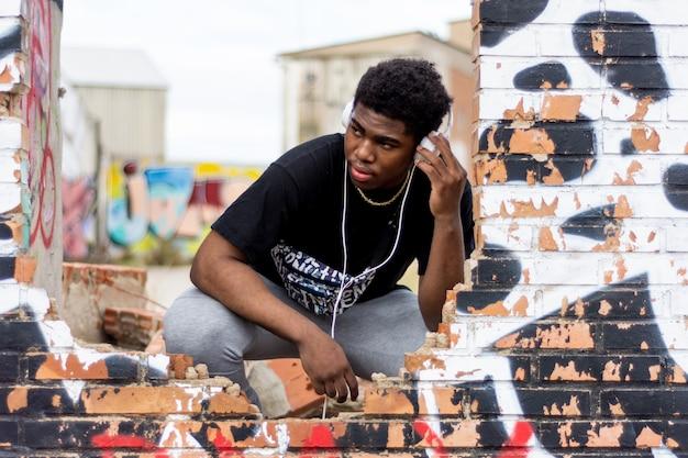 Portret van jonge zwarte jongen met witte hoofdtelefoons. naar muziek aan het luisteren. verlaten gebouw achtergrond.