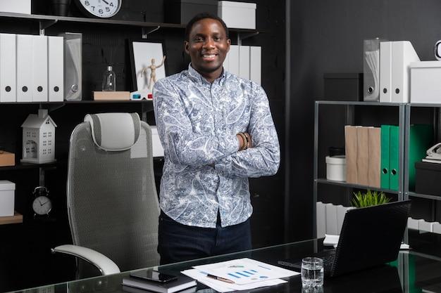 Portret van jonge zwarte zakenman die zich dichtbij lijst in bureau met zijn handen bevinden die op zijn borst worden gevouwen