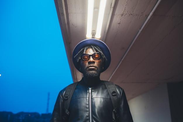 Portret van jonge zwarte zich in de straat bevinden en mens die camera kijken