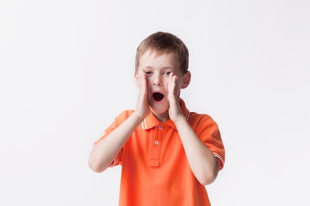Portret van jongen die met mond open status gilt dichtbij witte muur