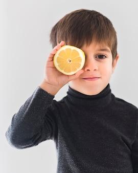 Portret van jongen die sinaasappel half over oog houdt