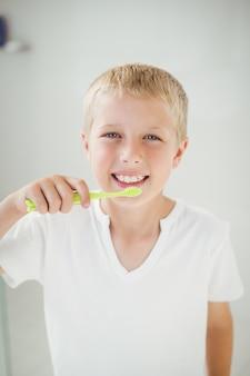 Portret van jongen die terwijl het poetsen van tanden glimlacht