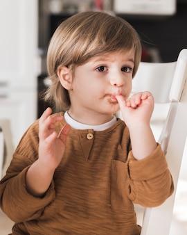 Portret van jongen die zijn vingers likt