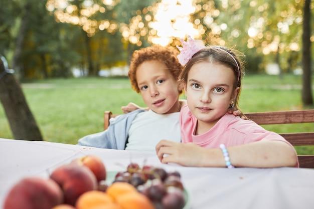 Portret van jongen en meisje die naar de camera kijken terwijl ze buiten aan de picknicktafel zitten, kopieer ruimte