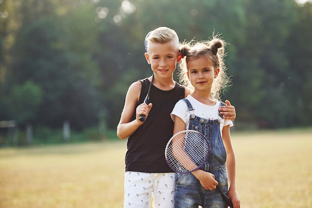 Portret van jongen en meisje die op zonnige dag in het veld staan met tennisrackets in handen.