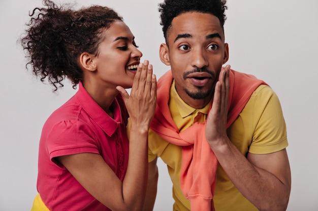 Portret van jongen en meisje in kleurrijke outfits roddelen op geïsoleerde muur
