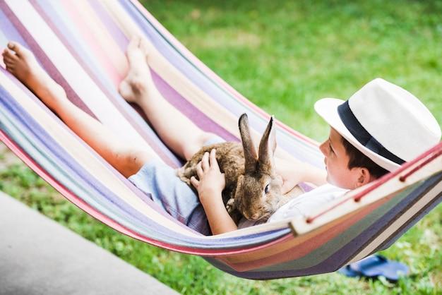 Portret van jongen liggend op hangmat met konijn in de hand