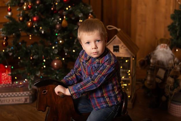 Portret van jongen speelgoed paard rijden in de buurt van de kerstboom feestelijk ingericht huis