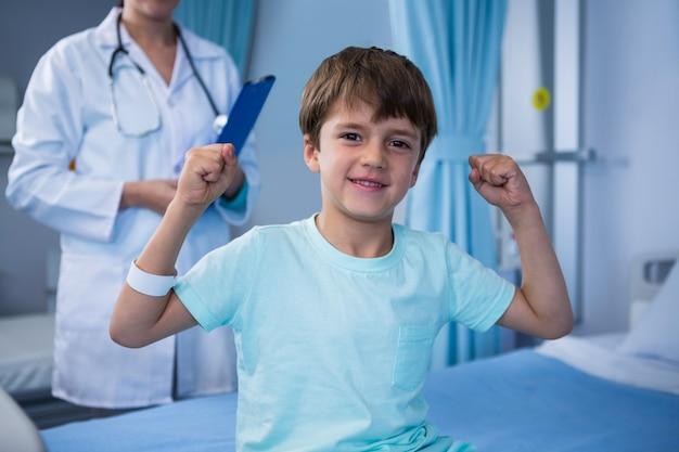 Portret van jongen zijn spieren buigen en vrouwelijke arts die zich op achtergrond bevinden