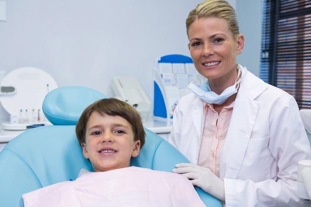 Portret van jongen zittend op een stoel door tandarts