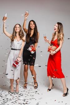 Portret van joviale zorgeloze mooie dames in cocktailjurken met glazen alcoholische dranken dansen en plezier maken onder vallende zilveren confetti