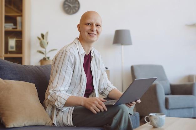 Portret van kale volwassen vrouw die lacht op camera tijdens het gebruik van laptop zittend op de bank in modern interieur, alopecia en kanker bewustzijn, kopie ruimte