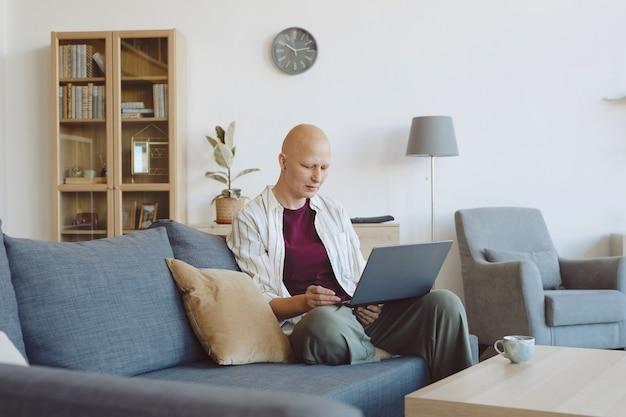 Portret van kale volwassen vrouw met behulp van laptop zittend op de bank in modern interieur, alopecia en kanker bewustzijn, kopie ruimte